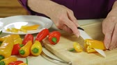 přípravě : Scene moves across an assortment of colorful veggies to the hands of a mature woman cutting up sweet yellow peppers.