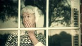 umma : View of a lonely elderly woman looking through a window waiting anxiously for someone to arrive 4k