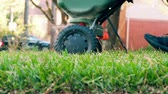 kordé : homeowner pushing a cart fertilizing his lawn slow motion