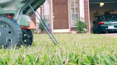 Homeowner fertilizing his lawn using a small manually operated fertilizer spreader. Slow motion.