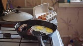 Man cooks breakfast of 4 eggs and 2 sausages in a large pan in the kitchen