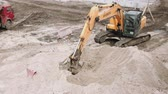 Powerful yellow excavator rakes the sand on the construction site