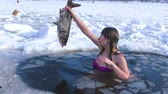 Woman winter swims in icy water. She is fishing. Vidéos Libres De Droits