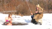 In winter, she catches fish under the ice water. Nearby is a winter fisherman.