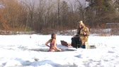 In the winter, a woman swims in the river with fish. She is not afraid of cold water. Wideo
