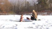 In winter, a woman swims in the icy water of the river. Nearby is a winter fisherman.