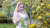 Young blond woman in the flower garden.