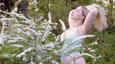 Young woman enjoys a spring morning in a flower garden. Vidéos Libres De Droits