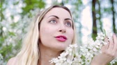Young beautiful woman stands among flowering bushes and smiling. Wideo