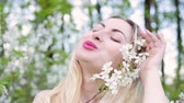 Young beautiful blonde woman stands among flowering bushes and admires nature. Wideo