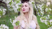 Beautiful blonde woman stroking a tree branch with flower buds in a blooming garden.