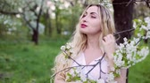 Beautiful young woman stands near a flowering tree in the garden. Wideo