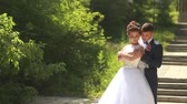 Beautiful happy young bride kissing handsome groom in sunlit park. Wedding couple in love