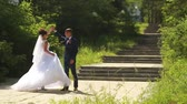 Happy handsome groom and beautiful bride in white dress dancing in the park