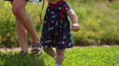 Adorable one year old Baby Girl making her first steps outdoor. First Steps of the Kid. Sunny day and Green Grass