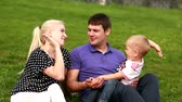 Happy family: father, mother and baby playing at grass