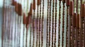 Wooden curtains flutter in draft in the doorway. A bamboo curtain sways in the wind. Handmade curtains of wooden beads near. Relaxing background with moving vertical sticks. Interior ecology elements 動画素材