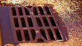 Drain metal grill on the road during the rain. Pig-iron rusty iron hatch with holes for rainwater drainage. Heavy rain at night on the roadway. Streams of rainwater flow down the drain
