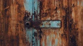 kifinomult : Abandoned garage. Old iron gate with peeling paint texture and scratches. Lots of locks and latches. Pan camera movement to top. Interesting texture. Feeling of danger and desolation. Stock mozgókép