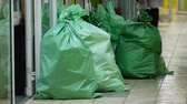 szövés : Large green sealed mail bags in the corridor. Plastic fabric polypropylene bags filled with goods or boxes lie on the floor.