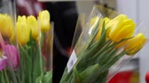 тюльпаны : Flowers in bouquets, tulips on the eve of March 8, International Womens Day holiday. Cash desk self-service. In the background, the buyer scans the goods at the terminal. Moscow, Russia