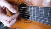 Enumeration of strings on an acoustic guitar of light brown color. Playing the instrument. Mens hands.