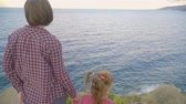 Mother and daughter standing on top of a mountain and looking at the sea. Sunset