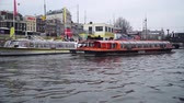 AMSTERDAM, HOLLAND - MARCH 3, 2018: Canal boats sail past March 3, 2018 in Amsterdam Стоковые видеозаписи