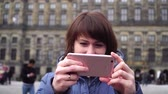 girl takes pictures on a smartphone on Dam Square. Amsterdam