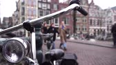 bisiklete binme : Bicycle is in Amsterdam close up. In the background people walk around the city