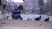 girl feeds ducks near a pond in a park in Amsterdam