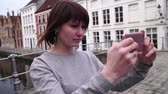 belçika : Woman tourist takes pictureson on smartphone in Bruges Belgium. slow motion