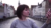 smartfon : girl tourist doing selfie on smartphone at sunset in Bruges Belgium. Wideo