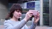 parlament : Woman tourist takes pictureson on smartphone near the European Parliament in Brussels. Belgium.