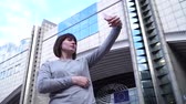 economics : Lady tourist make selfie on smartphone near the European Parliament in Brussels. Belgium. slow motion. Stock Footage