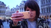 fotografie : Lady tourist takes pictures on Grand-Place in Brussels, Belgium.slow motion. dolly zoom effect