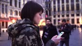 smartfon : Tourist girl walks and looks at attractions on Grand-Place in Brussels, Belgium