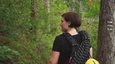 View from the back to traveler woman hiking on forest trail path in mountain .slow motion