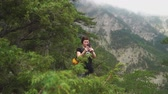 Woman traveling, making photo of beautiful green forest and mountains nature landscape on smart phone. slow motion Stock mozgókép