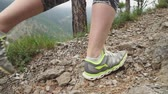 View of feet of traveler walking on top of cliff in mountains on summer day .slow motion