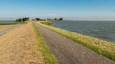 Uitdam, The Netherlands - September 11, 2015: Time lapse or bicycle path on a Dutch dike at transpiring with cyclists. Dostupné videozáznamy