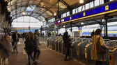 kapu : Nijmegen, Netherlands - November 7, 2017: Public transport gates at railway central station Nijmegen with travellers and trains at the platform. Stock mozgókép