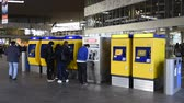 Rotterdam, The Netherlands - March 10, 2017: Travelers getting their tickets at the ticket machine at the railway station of Rotterdam in the Netherlands.