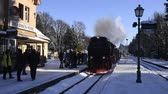 Drei Annen Hohe, Germany - February 5, 2018: Steam locomotive of the Harzer Schmallspurbahnen in wintertime coming to the station with people waiting.
