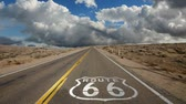 rota : Route 66 highway pavement sign with time lapse clouds.