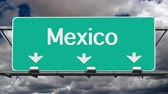 скрестив : Mexico border crossing highway sign with time lapse clouds.