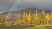 Cold orange autumn morning fog with rainbow and tent in the mountains Dostupné videozáznamy
