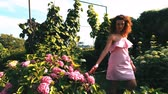 ás : Young attractive woman walk near flowers and touch blooms in garden