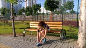 марафон : Beautiful girl is sitting on the bench in the park, preparing to run