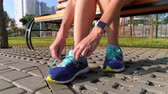 jogging yapan : Girl is sitting on a bench, preparing to run. Sportswearshoes close-up Stok Video
